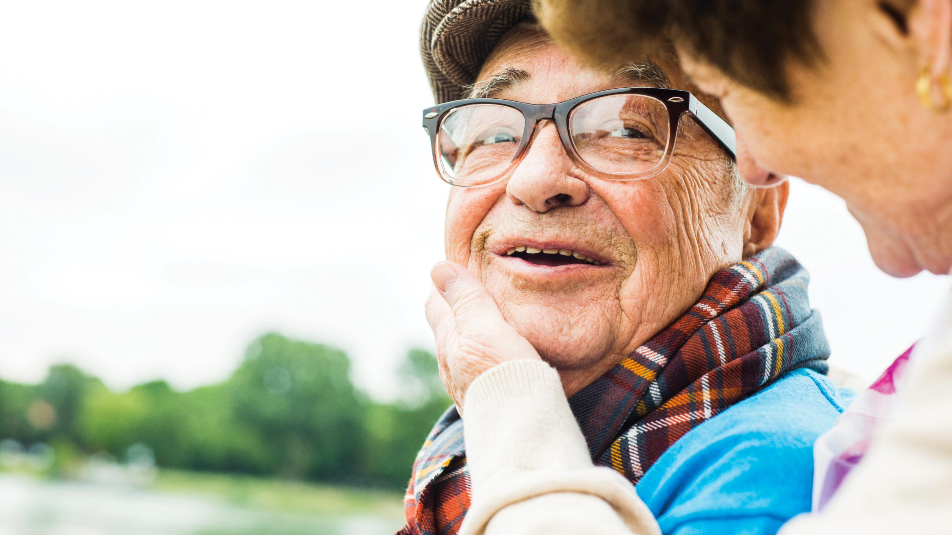 Image of an elderly man outdoors, and a woman beside him who is patting his cheek