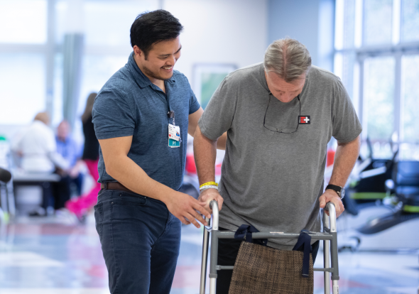 Health care worker assisting a patient using a walker