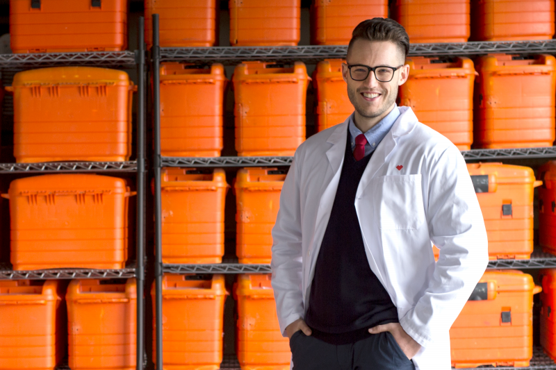 An Omnicare representative standing in front of shelves full of bins use to deliver patient medication