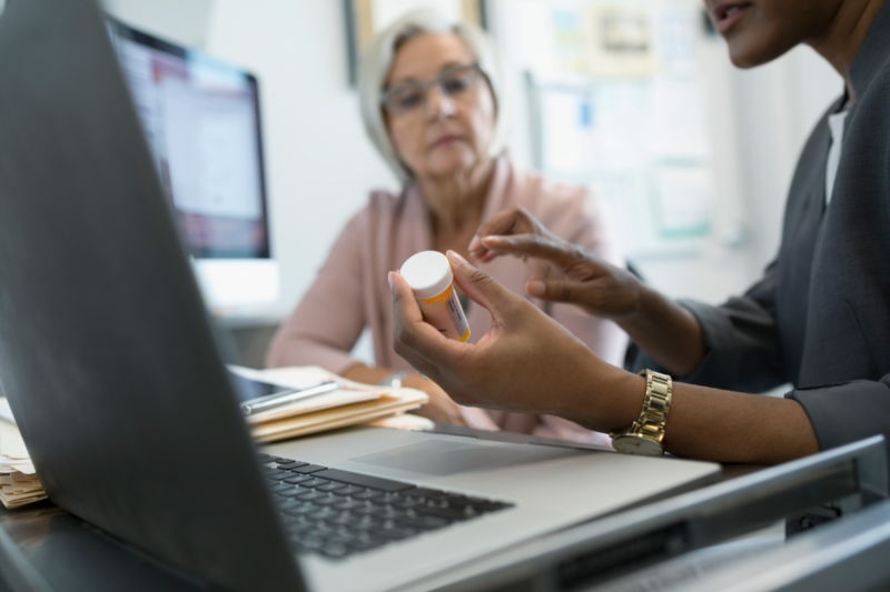 A CVS Pharmacy representative at a computer discussing a vial of medication with an elderly woman
