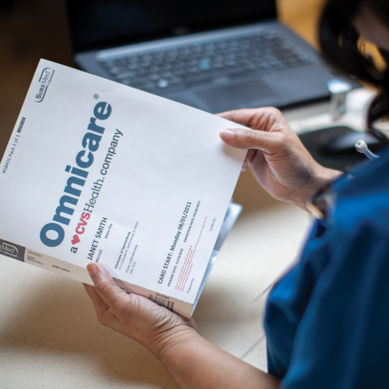 woman holding a patient medication record from Omnicare